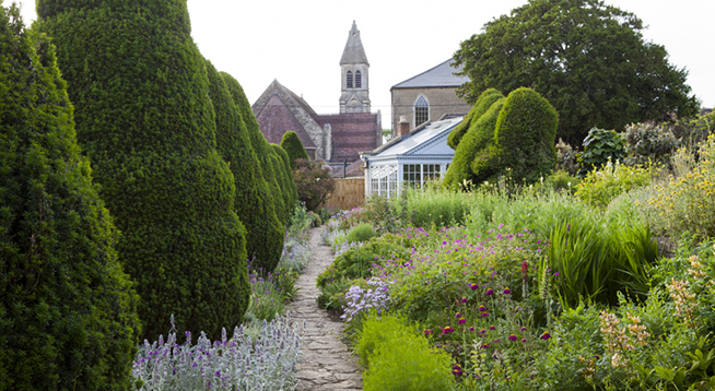 The Yew Walk at The Courts Garden, Wiltshire, in June. The church in view in the distance is not National Trust.